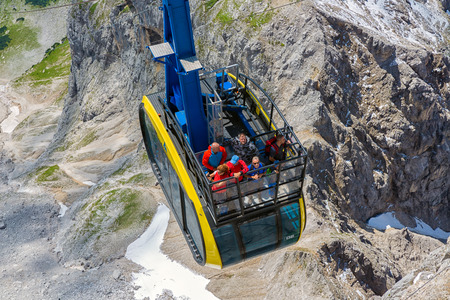 DACHSTEIN MOUNTAINS, AUSTRIA - JULY 17, 2017: Aerial view cable car approaching the Dachstein glacier mountain station in Austria. Some people are standing at the balcony at the roof of the cable car Éditoriale