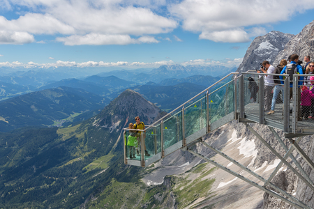DACHSTEIN MOUNTAINS, AUSTRIA - JULY 17, 2017: Dachstein Mountain in Austria with hikers taking pictures at a view platform of a steel skywalk rope bridge 新聞圖片