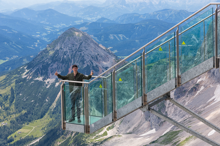 DACHSTEIN MOUNTAINS, AUSTRIA - JULY 17, 2017: Young man with thumbs up at view platform of skywalk rope bridge Dachstein Mountains in Austria Editorial