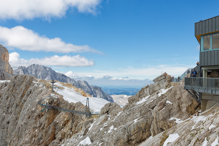 DACHSTEIN MOUNTAINS, AUSTRIA - JULY 17, 2017: Dachstein Mountain in Austria with hikers passing a steel skywalk rope bridge near the glacier top station Editorial
