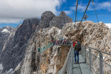 DACHSTEIN MOUNTAINS, AUSTRIA - JULY 17, 2017: Dachstein Mountain in Austria with hikers passing a steel skywalk rope bridge Editorial