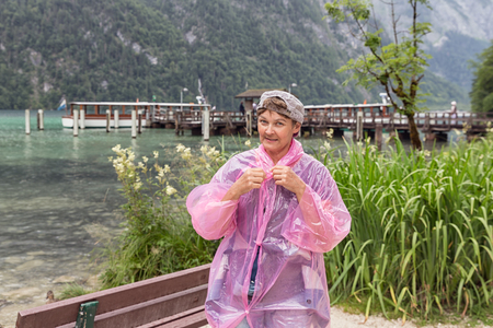 Woman with raincoat at coast of Konigssee near Berchtesgaden in German Alps