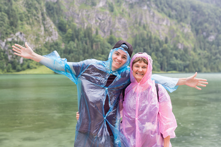 Mother and son with raincoats at coast of Konigssee near Berchtesgaden in German Alps