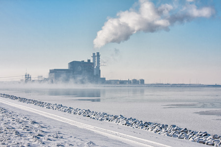 Dutch frozen lake covered with haze and view at a power plant