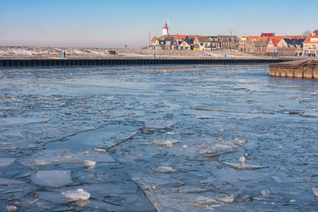 Dutch fishing village Urk in winter with frozen harbor and view at the lighthouse