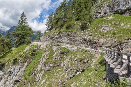 WERFEN, AUSTRIA - JULY 19, 2017: People walking at hiking trail through Austrian mountains near Werfen to ice cave Eisriesenwelt