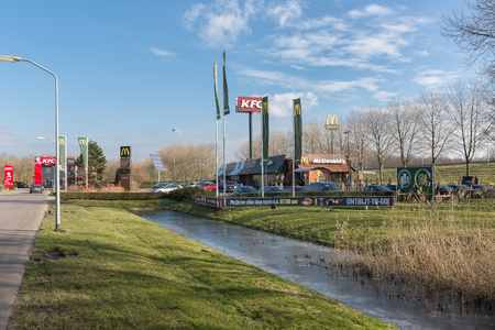 Lelystad, The Netherlands - February 22, 2018: Car park near Dutch motorway with fastfood restaurants Mc Donalds and KFC