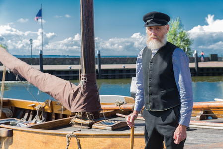 Urk, The Netherlands - September 02, 2017: Old sailor with stick, cap and beard standing for traditional wooden fishing boat in Dutch harbor of Urk 報道画像