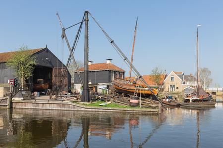 Historical ships at shipyard with slipway in harbor Dutch fishing village Workum