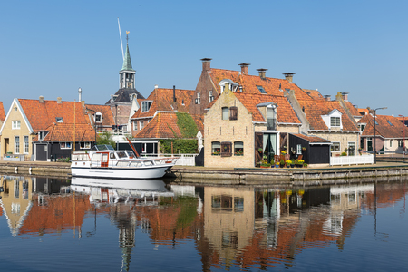 Facade of Houses along a canal in Makkum, an old Dutch village in Friesland