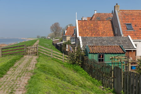 Traditional houses along a dike in Makkum, an old Dutch fishing village in Friesland Stockfoto
