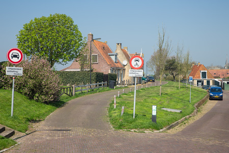 Traditional houses with road signs in Makkum, historic Dutch fishing village in Friesland Stock Photo