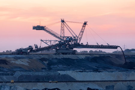 Sunset landscape brown coal open pit with digging machine in Hambach mine Germany
