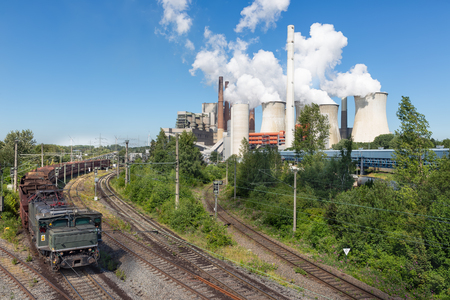 Coal-fired power plant with rempty cargo train near Garzweiler open pit mine in Germany Stock Photo
