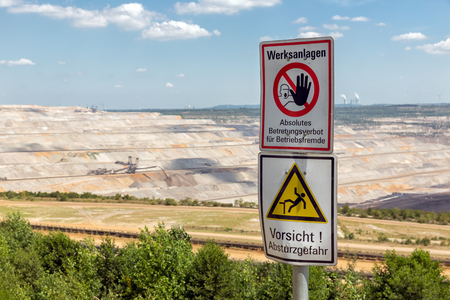 Warning sign near open pit mine Hambach with brown coal digging in Germany Imagens