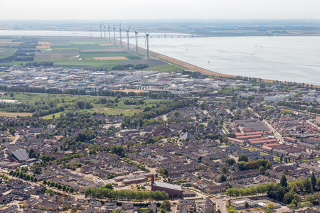 Aerial view Dutch fishing village with new build residential area and wind turbines along the coast