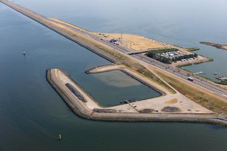 Aerial view service harbor along Dutch dike Afsluitdijk, separation between the fresh water lake IJsselmeer and the salt Wadden Sea