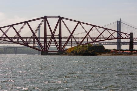 Forth railway Bridge and two road bridges in backlight over Firth of Forth near Edinburgh , Scotland