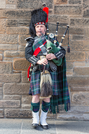 Edinburgh, Scotland - May 24, 2018: Man in traditional Scottish clothing playing bagpipe at the Royal Mile in Edinburgh