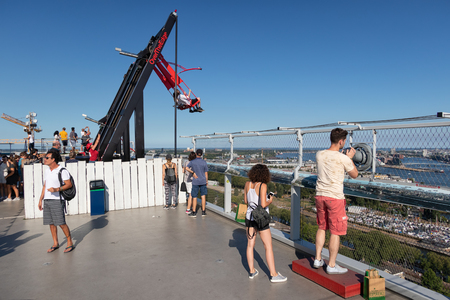 Amsterdam, The Netherlands - August 03, 2018: People at observation deck with swing at the top of a skyscraper building downtown in Amsterdam