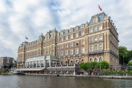 Amsterdam, The Netherlands - June 19, 2018: View at famous five star Amstel hotel at the bank of the Amstel river, The Amstel Hotel is part of the InterContinental Hotels chain