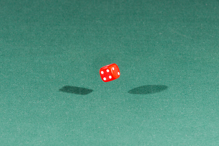 One red dice falling on a isolated green table
