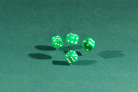 Four green dices falling on a isolated green table Stock fotó
