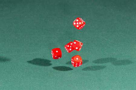 Five red dices falling on a isolated green table Stock Photo