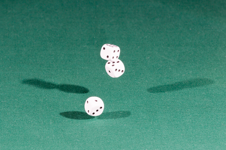 Three white dices falling on a isolated green table
