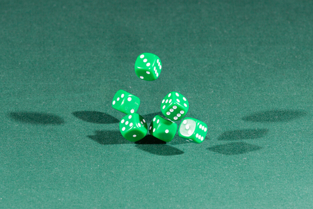Six green dices falling on a isolated green table