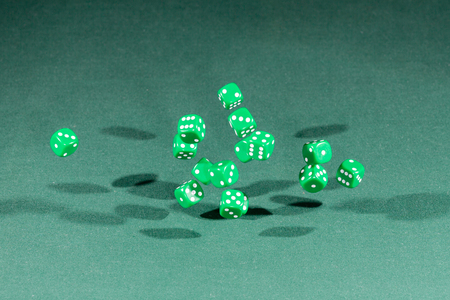 Fifteen green dices falling on a isolated green table