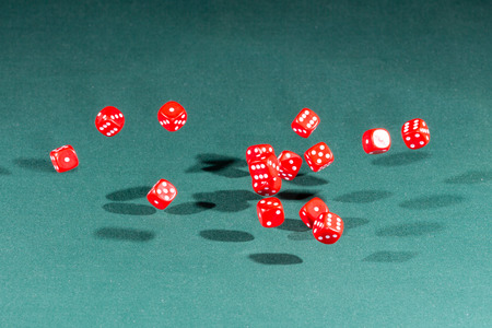 Fifteen red dices falling on a isolated green table