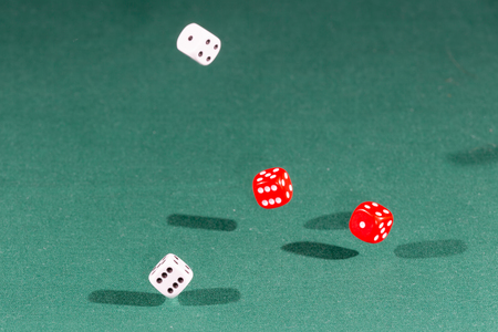 Four red and white dices falling on a isolated green table