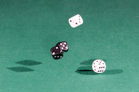 Four white and black dices falling on a isolated green table Фото со стока
