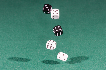 Five white and black dices falling on a isolated green table