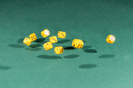 Ten yellow dices falling on a isolated green table