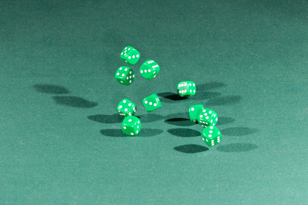 Ten green dices falling on a isolated green table Фото со стока