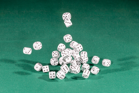 Thirty white dices falling on a isolated green table