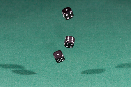 Three black dices falling on a isolated green table