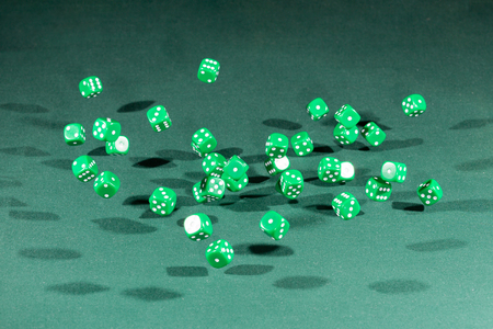 Thirty green dices falling on a isolated green table