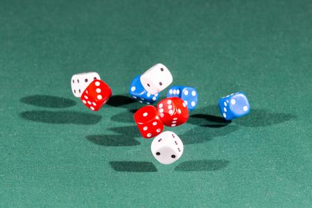 Nueve dados blancos, rojos y azules cayendo sobre una mesa verde aislada Foto de archivo