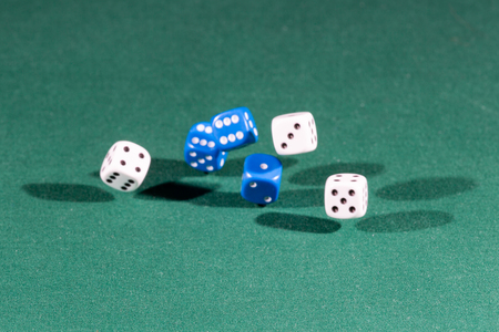 Six white and blue dices falling on a isolated green table