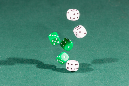 Six white and green dices falling on a isolated green table