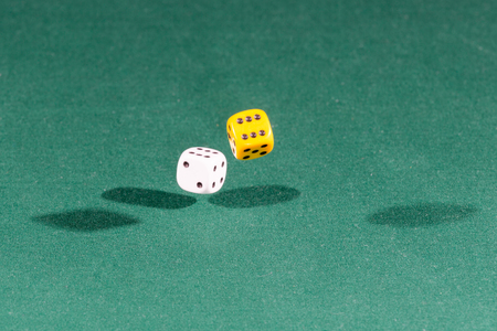 Two white and yellow dices falling on a isolated green table Фото со стока
