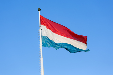 Flag of Luxembourg waving in the wind against a blue sky
