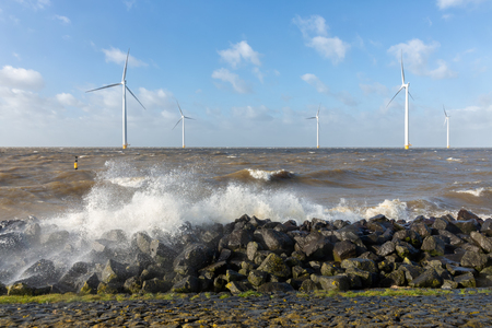 Dutch sea with off shore wind turbines and breaking waves at the shore Stockfoto - 118514185