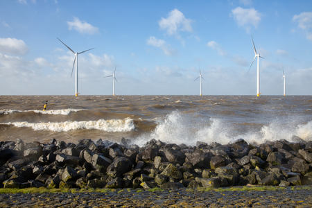 Dutch sea with off shore wind turbines and breaking waves at the shore Stockfoto - 118514186