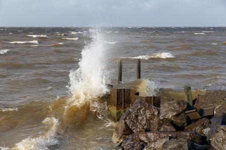 Dutch breakwater in IJsselmeer Flevoland with breaking wave in heavy storm Stock Photo