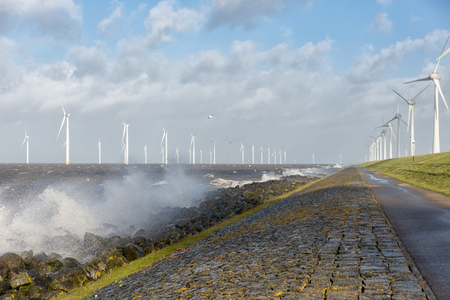 Dutch sea with off shore wind turbines and breaking waves at the shore Stock Photo