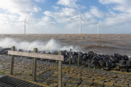 Dutch sea with off shore wind turbines and breaking waves at the shore Foto de archivo